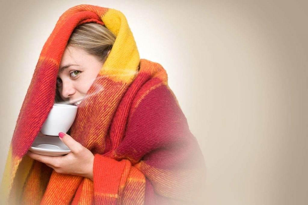 Battaniyeye sarılmış bitki çayı içen kadın